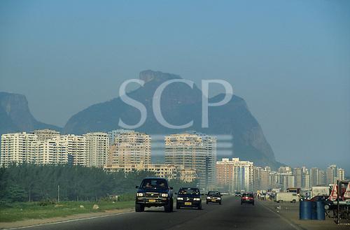 Barra da Tijuca, Rio de Janeiro, Brazil. High-rise appartment blocks and cars driving on a wide road.