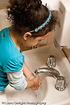 Education Preschool 4-5 year olds health and hygiene girl washing her hands in bathroom sink vertical
