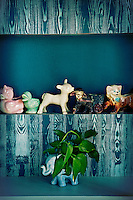 A kitsch display of pottery animal figures are displayed on a blue unit.