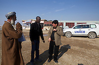 UNVs discussing the planning of a new school in Noor-Abad with the community leader