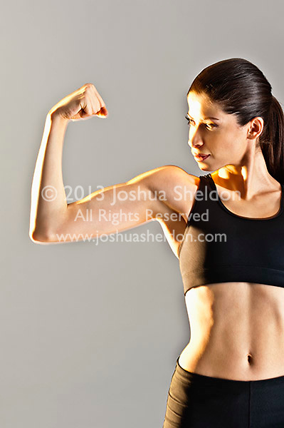 Young Caucasian woman wearing black sports clothing flexing muscles