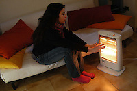 Ragazza si scalda con stufetta elettrica a causa della crisi energetica..Girl heats with electric stove because of the energy crisis....