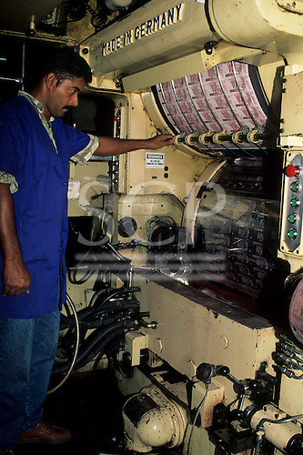 Rio de Janeiro, Brazil. Worker tending printing machine, printing Real currency notes.