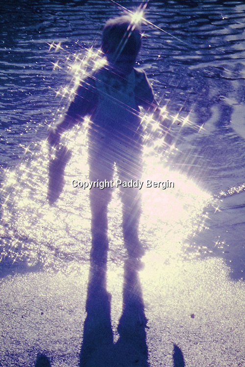 Reflection of boy silhouetted by sunlight. Paddling in water with Wellingtons on.<br /> <br /> Stock Photo by Paddy Bergin