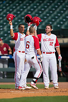 Brett Kinneman (6) of the North Carolina State Wolfpack celebrates at home plate with teammates Joe Dunand (left) and Brad Debo (12) after hitting a 3-run home run against the Boston College Eagles in Game Two of the 2017 ACC Baseball Championship at Louisville Slugger Field on May 23, 2017 in Louisville, Kentucky.  The Wolfpack defeated the Eagles 6-1. (Brian Westerholt/Four Seam Images)