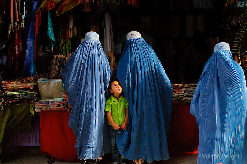 """Mazar-E-Sharif, Afghanistan<br /> Are you my mother?   <br /> I watched with amusement as this young child grabbed the hems of a few burkas before zoning in on her mother in a busy market place. As I moved through the cities and around the countryside women threw their burkas over my head. Ensconced in our secret tents they would kiss me three times on my cheeks and thank me for me for coming. I was often invited back into their homes with them where we would secretly share a cup of cardamom tea. <br /> <br /> Friday, a Muslim holiday, is a day off for everyone. Shops close, it is a day of rest. I soon discovered where the women go: Bagh-E-Zanana, commonly called the Women's Park. No men allowed. A small unkempt publicly owned area of land, it is a sacred space for women. Off come the shawls and burkas. The women are adorned in brightly colored dresses, long painted fingernails and heavy jewelry. They bring small picnics and snacks, beat tamborines, dance and gossip. They trade makeup, sunglasses and beauty tips. The young girls express themselves in clothes they would never dare to wear in public; hip hugging jeans, tight blouses, and they literally let their hair down. It is here, that on one day of the week, on one dry little patch of land in the corner of Kabul, the women of Afghanistan are free to throw off their burkas and dance.<br /> <br /> Afghanistan is such a beautiful country. I wanted to attempt to bring a face to the place, to portray a slice of life beyond a war zone. Still, it's obviously a challenging and dangerous place to photograph. Before I'd get in the car my driver would always scan underneath the vehicle for car bombs. Then he'd turn the key in the ignition with a prayer, """"Inshallah."""" God willing.<br /> """"OK,"""" I eventually told him, """"You really need to stop doing that because it's kind of starting to freak me out."""""""