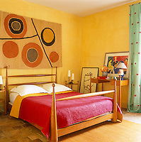 Bright yellow walls reflect back the Provencale sun in this cheerful bedroom where a quilt in the traditional red and yellow covers the bed
