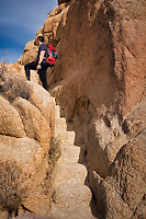Hiker on trail with steps carved into granite. Joshua Tree National Park, California