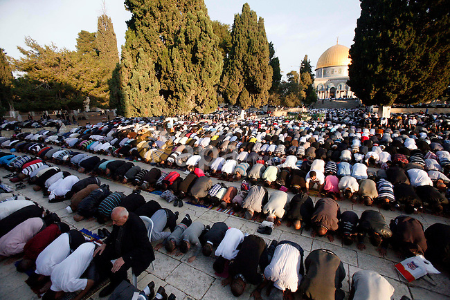 Palestinian Muslim worshippers pray at the al-Aqsa Mosque compound in Jerusalem's old city on the first day of Eid al-Adha on October 26, 2012 as Muslims worldwide commemorate Eid al-Adha, or the Feast of the Sacrifice, marking the end of the hajj and commemorating Abraham's willingness to sacrifice his son Ismail on God's command. Photo by Mahfouz Abu Turk