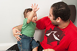 10 month old baby boy sitting with older brother age 20, gesturing and talking