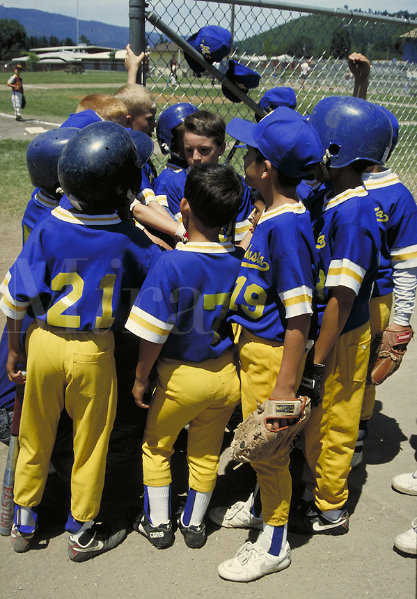 Young boys wearing uniforms at tee-ball game. California.