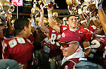 While his Seminole team does a chant with helmets raised, coach Bobby Bowden flashes a smile after Michael Boulware (L) and Chris Rix (R) presented him with a commemorative football declairing him the winningest Division 1 active college football coach in America with 339 wins. (Mark Wallheiser/TallahasseeStock.com)