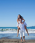 USA, California, San Francisco, man giving woman piggy back on Baker Beach