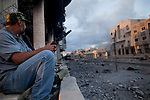 A revolutionary fighter stands guard on Dubai Street, where pro-Gaddafi snipers took up positions and caused many casualties, in central Sirte, Libya, Oct. 13, 2011. Revolutionary forces solidified control of the pro-Gaddafi stronghold, but fighting continued in a few neighborhoods.