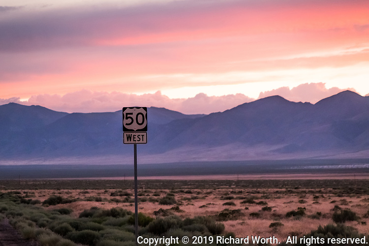 """The highway sign identifying U.S. Route 50, at sunset, along a deserted stretch of what is called, """"The Lonliest Road in America"""" in the desert between Austin and Fallon, Nevada."""