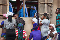 """Nigeria. Abakaliki State. Uburu Amach. St. Patrick's Catholic Church. Igbo people pray during the mass celebration for the 25th Priesthood Anniversary of Reverend Father Edward Inyanwachi. All women a head tie which is a women's cloth head scarf. The head tie is used as an ornamental head covering or fashion accessory, or for functionality in different settings. Its use or meaning can vary depending on the country and/or religion of those who wear it. The head tie is called gele in Nigeria. A group of sisters from """"Sisters of Jesus the Good Shepherd"""" attend the mass inside the church. The Sisters of Jesus the Good Shepherd, also known as the Pastorelle Sisters, is a Catholic religious order with the motto: """" Love and service of the people of God in imitation of Jesus the Good Shepherd"""". 14.07.19 © 2019 Didier Ruef"""