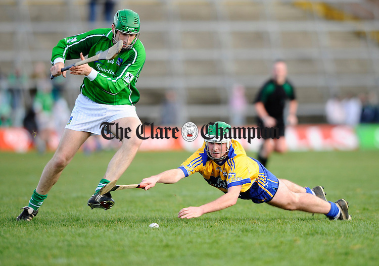 Limericks Sean O Connor tries to keep the ball away from a fallen Tommy Holland of Clare during their National League game in Limerick. Photograph by John Kelly.