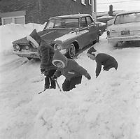 Enfants et adultes pelletent la neige pour degager une voiture PLYMOUTH ,durant une tempete de neige, novembre 1965 (date exacte inconnue, possiblement vers le 18) dans la ville Quebec.<br /> <br /> PHOTO : Agence Quebec Presse