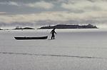 A man walks carefully across thin ice towing a canoe.