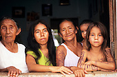 Altamira, Para State, Amazon, Brazil. Four generations of Xipaya Indian women looking through an open window. Some with body paint.
