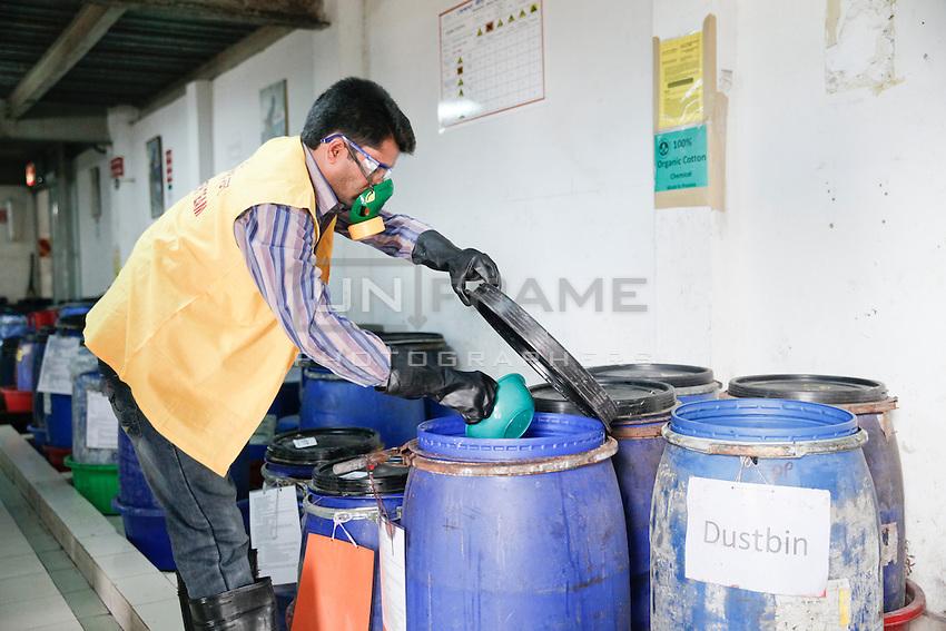 A man checks the chemical used for dying the fabrics.  Gazipur, near Dhaka, Bangladesh