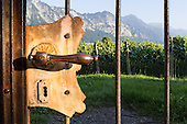Switzerland. Old metal door handle in gate to vineyards with mountains.