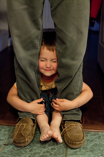 Eli, almost four, hugs his dad's legs when Ted returns home after a weekend of working.