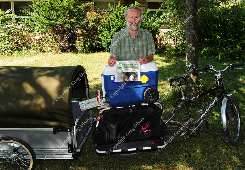 George Zens delivers the Sustainable Times with his customized bicycle that includes a trailer he purchased from Canada, as it was unavailable in the USA. Zens poses in front of his home office on Saturday in Middleton, Wisconsin