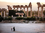 July 2010, LEBANON: A burqua clad woman walks with a small boy past  a colonnaded archway amidst the Bekaa Valley's famed Roman ruins.Picture by Graham Crouch