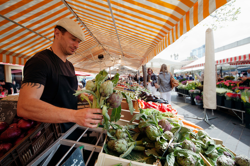 Chef Giorgio Grilenzoni of the 'Chat Noir, Chat Blanc' restaurant chooses locally-grown artichokes at the Cours Saleya market, Nice, France, 10 April 2012