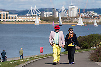 CARDIFF, UK. 2nd April 2017. A man and woman walk hand-in-hand along the Cardiff Bay barrage in sunny weather.