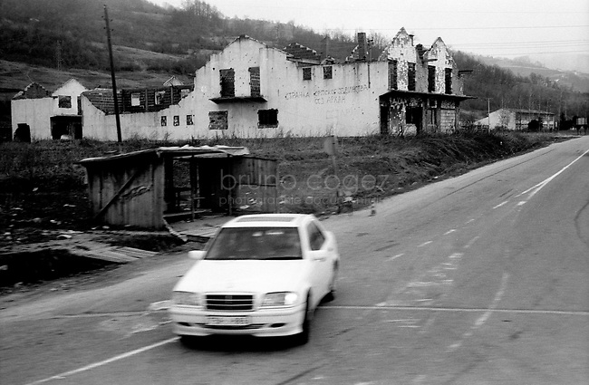 BOSNIA-HERZEGOVINA, Belgrade-Sarajevo Road, 03/2003..Lanscape pictures taken from the bus between Belgrad and Sarajevo. .Mercedes car in streets of the village of Nova Kasaba, ex muslim enclave. In the background, houses destroyed during the war.  .BOSNIE-HERZEGONVINE, Route Belgrade-Sarajevo, 03/2003..Photo prise depuis le bus qui relie Belgrade à Sarajevo. Une Mercedes dans les rues du village de Nova Kasaba, ancienne enclave musulmane. En arrière plan, des maisons détruites pendant la guerre..© Bruno Cogez