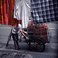 A Chinese worker unloads goods from a tricycle in front of some laundries hanging up by local residents in Shanghai in June 2011. (Mamiya 6, 75mm f3.5, Kodak Ektar 100 film)