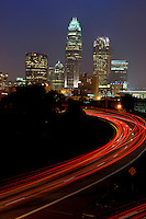 Car break lights streak into the city as uptown Charlotte NC is seen is at twilight.