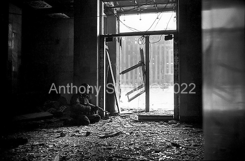 Grozny, Chechyna.January 1995.A young Russian soldier stands guard ove rthe Presidentual Palace from the Hotel Kovkaz. It was taken just taken just hours before, when Chechen fighters fled. It remains under heavy sniper fire from the Chechen resistance.