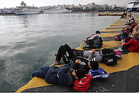 Pictured: Migrants rest at the port Friday 26 February 2016<br /> Re: Hundreds of refugees that crossed the border from Turkey to the Greek islands, have arrived at the port of Piraeus near Athens, Greece