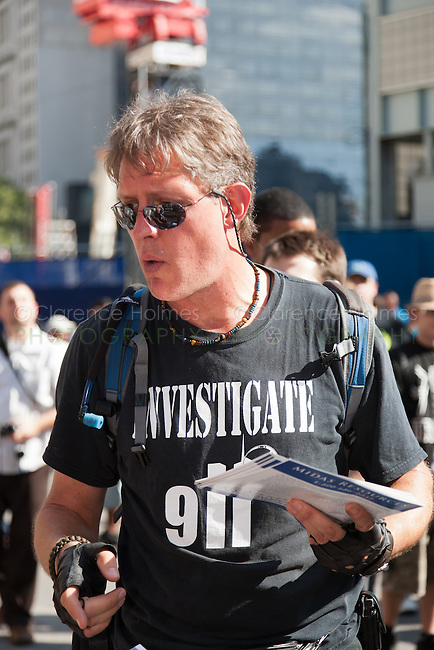 """A protester wearing an """"Investigate 911"""" shirt hands out literature at the WTC PATH station."""