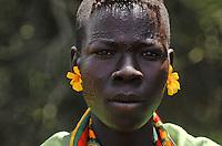 UGANDA Karamoja , Karimojong a pastoral tribe , young woman with facial ornament / UGANDA Karamoja , Volk der Karimojong , junge Frau mit Gesichtsverzierung und Blumen am Ohr waehrend einer christlichen Sonntagsmesse