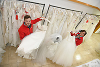 """Pictured: Staff members, Jonathan Beasley and Jo Williams pictured amongst the wedding dresses on offer at John Pye Auctions in Pyle, south Wales, UK.<br /> Re: A bride cried tears of joy after her missing wedding dress was found among a pile of 20,000 gowns in a warehouse.<br /> Meg Stamp, 27, paid £1,300 for the beautiful ivory lace dress but it  was seized by liquidators after a bridal company went bust.<br /> It was boxed up along with 20,000 others and due to be sold for a knock-down price at auction.<br /> But determined Meg banged on the auctioneer door saying: """"I want my dress back"""".<br /> Staff at John Pye auctioneers in Port Talbot spent three hours sifting through boxes until they finally found Meg's dream dress."""