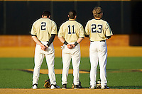 Mark Rhine (2), Pat Blair (11) and Jimmy Redovian (23) during the National Anthem prior to the game against the North Carolina State Wolfpack at Wake Forest Baseball Park on March 15, 2013 in Winston-Salem, North Carolina.  The Wolfpack defeated the Demon Deacons 12-6.  (Brian Westerholt/Four Seam Images)