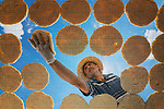 """Pictured: A villager in Tokat, Turkey, carefully places tarhana dough on a mesh to dry out in the sun.<br /> <br /> Tarhana is a dried food ingredient, based on a fermented mixture of grain and yoghurt or fermented milk, found in the cuisines of Southeast Europe and the Middle East.<br /> <br /> The image was taken by Suleyman Uzumcu, 34, from Tokat.<br /> <br /> Suleyman said, """"This is a traditional dish in the region.  After the drying, it is usually made into soup and local villagers prepare them to eat in the winter months.""""<br /> <br /> """"The drying time varies according to the weather, but it usually takes one day. A kilo of tarhana is sold in the markets for 25 Turkish liras.  Familes who produce the, sell them at local markets""""<br /> <br /> Please byline: Suleyman Uzumcu/Solent News<br /> <br /> © Suleyman Uzumcu/Solent News & Photo Agency<br /> UK +44 (0) 2380 458800"""