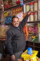 India, Dehradun.  Shopkeeper Reaching for a Jar of Cardamon Seeds.