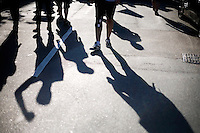 Shadows are visible on the street as OccupyBoston protesters walk through the streets of the Back Bay area of Boston, Massachusetts, USA.  The area is a high-traffic shopping area. The protesters are part of  OccupyBoston, which is part of the OccupyWallStreet movement, expressing discontent with the socioeconomic situation of the 99% of the US population who are not wealthy.  Protestors have been camping in Dewey Square since Sept. 30, 2011. Gradually, larger organizations, including major labor unions, have expressed their support for the OccupyBoston effort.