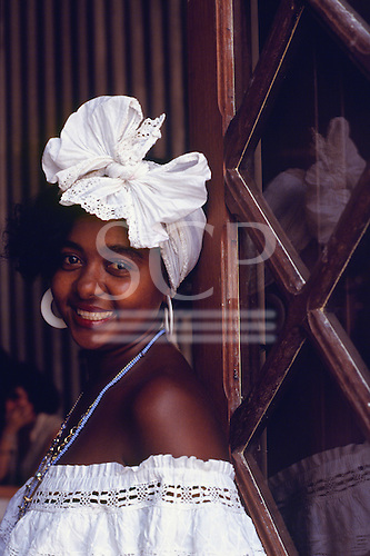 Salvador, Bahia, Brazil. Smiling Bahiana woman wearing traditional white dress and knotted headscarf.