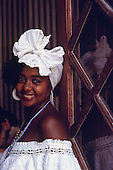 Salvador, Bahia, Brazil. Smiling Bahiana woman wearing traditional white dress and knotted headscarf.