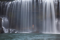 Visitor standing behind Kilauea Falls, a gem of a waterfall even by Kauai standards