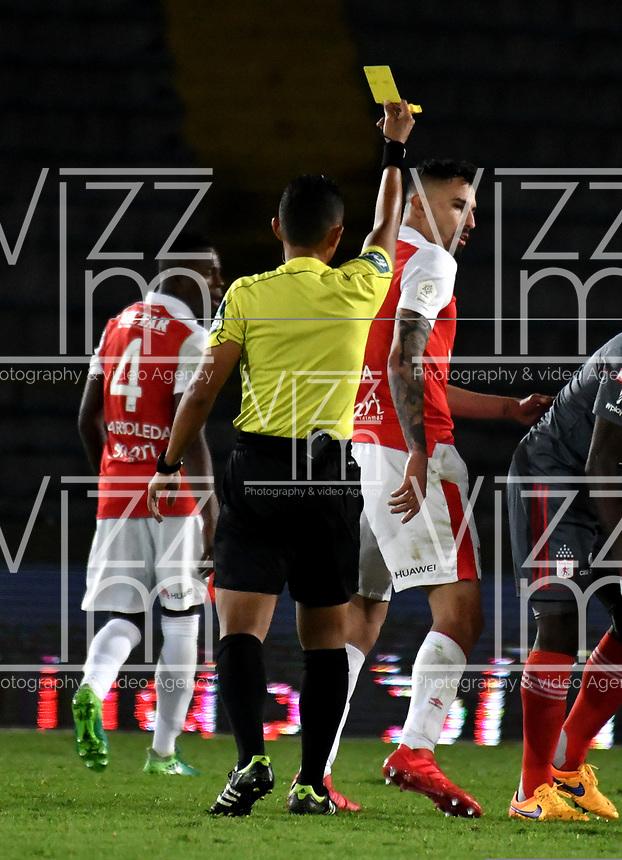 BOGOTA - COLOMBIA - 21 - 03 - 2018: Bismarks Santiago (Izq.), arbitro, muestra tarjeta amarilla a Jose Moya (Der.), jugador de Independiente Santa Fe, durante partido aplazado de la fecha 3 entre Independiente Santa Fe y America de Cali, por la Liga Aguila I 2018, en el estadio Nemesio Camacho El Campin de la ciudad de Bogota. / Bismarks Santiago (L), referee, shows yellow card to Jose Moya (R) player of Independiente Santa Fe, during a posponed match of the 3rd date between Independiente Santa Fe and America de Cali, for the Liga Aguila I 2018 at the Nemesio Camacho El Campin Stadium in Bogota city, Photo: VizzorImage / Luis Ramirez / Staff.