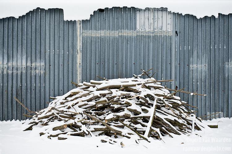 Firewood is piled outside a shed on Mirosława Horodiuk's farm.