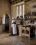A pensive kitchen maid is smelling a spring of rosemary at the sink. The high window at Canons Ashby prevents servants from seeing out. (M.R.)