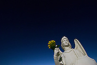 A statue of St. Matthias with a plastic  sunflower in his hand.<br />